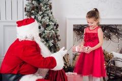 打开礼物的圣诞老人和孩子在壁炉 孩子在服装佩带的胡子开放圣诞节礼物生 库存照片