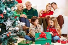 打开礼物的孩子在圣诞节 免版税库存图片