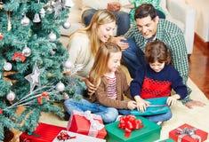 打开礼物的孩子在圣诞节 免版税库存照片