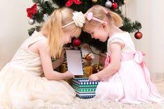 打开礼物盒的两个小女孩在圣诞树附近 免版税库存图片