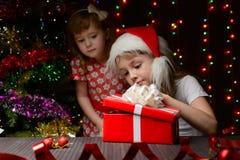 打开礼物盒的圣诞老人帽子的女孩 库存图片