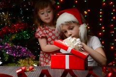 打开礼物盒的圣诞老人帽子的女孩 库存照片