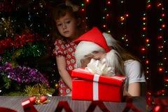 打开礼物盒的圣诞老人帽子的女孩 免版税库存照片