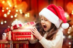 打开礼物盒的圣诞老人帽子的愉快的女孩 免版税图库摄影