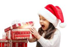 打开礼物盒的圣诞老人帽子的愉快的女孩 库存图片