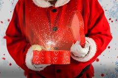 打开礼物盒的圣诞老人的综合图象 库存照片