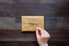 打开礼物盒的女性手包裹与工艺纸和花在木台式视图 礼物为任何假日 免版税库存照片