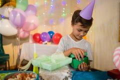 打开礼物盒的男孩在生日聚会期间 库存照片