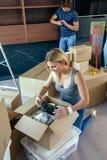 打开移动的箱子的妇女 图库摄影