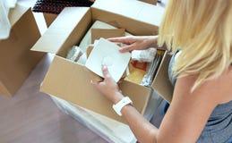 打开移动的箱子的妇女 库存照片
