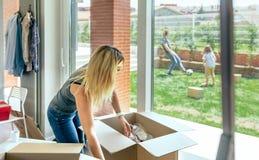 打开移动的箱子的妇女 免版税库存图片