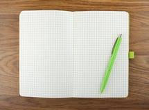 打开空白有绿色笔的被检查的笔记本在桌上 免版税库存照片