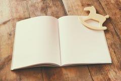 打开空白的笔记本和木摇马玩具在木桌 为大模型准备 减速火箭的被过滤的图象 库存图片