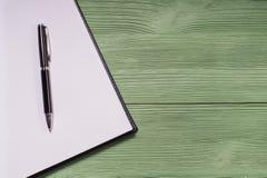 打开空白的笔记本和笔在绿色木背景 库存图片
