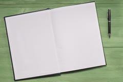 打开空白的笔记本和笔在绿色木背景 免版税库存图片