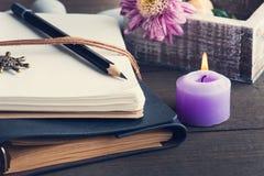 打开空白的笔记本,被点燃蜡烛,花 免版税库存照片