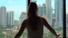 打开窗口的帷幕的一名成功的富有的妇女的剪影忽略与摩天大楼的市中心 股票视频