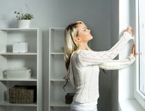 打开窗口的年轻和美丽的白肤金发的妇女 库存照片