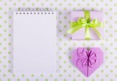 打开笔记本、心脏origami和蛋白软糖棍子在圆点背景  免版税库存照片