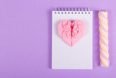 打开笔记本、心脏origami和蛋白软糖棍子在紫色背景 库存图片
