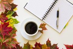 打开笔记本、笔和咖啡,构筑与在白色背景的秋叶 平的位置 顶视图 空的拷贝 免版税库存照片