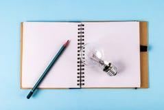 打开笔记本、笔和电灯泡,博克概念图象 库存照片