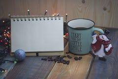 打开笔记本、蓝色在tablenn的杯子和圣诞节玩具雪人 免版税图库摄影