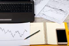 打开笔记本、玻璃、计算机、笔和智能手机在一张木桌上 免版税图库摄影