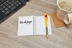 打开笔记本与西班牙文本` DIA DE PAGA `发薪日和一杯咖啡在木背景的 库存图片