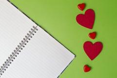打开笔记本和红色心脏在绿叶背景 背景蓝色框概念概念性日礼品重点查出珠宝信函生活纤管红色仍然被塑造的华伦泰 顶视图 复制空间 免版税库存照片