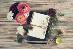 打开笔记本和花装饰 库存照片