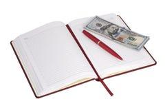 打开笔记本和金钱 图库摄影