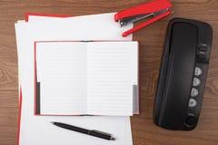 打开笔记本和黑电话在木纹理 免版税库存照片