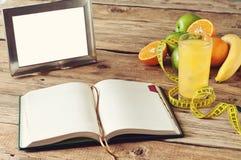 打开笔记本,果子,在桌上的汁液 图库摄影