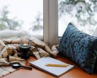 打开笔记薄、放大器玻璃、枕头、蜡烛、铅笔和格子花呢披肩 图库摄影