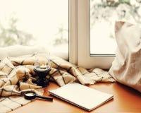 打开笔记薄、放大器玻璃、枕头、蜡烛和米黄温暖的pla 免版税图库摄影
