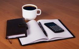打开笔记薄、组织者、计算器和杯子  免版税库存照片