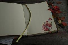 打开笔记薄以木背景的秋天烹饪贴纸基于 库存照片