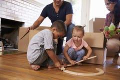 打开箱子的家庭在新的家在移动的天 图库摄影