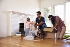 打开箱子的家庭在新的家在移动的天 库存照片