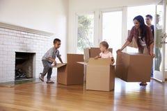 打开箱子的家庭在新的家在移动的天 库存图片