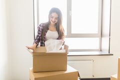 打开箱子的愉快的少妇在新的家 移动的comcept 库存照片