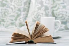 打开精装书书,在木桌上的杯子 自然本底 回到学校 复制文本的空间 库存图片