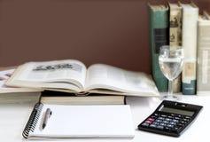打开精装书和课本堆积与在tabl的一个计算器 图库摄影