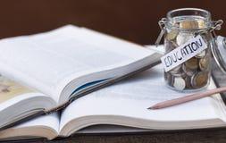 打开精装书或课本被堆积的和在tabl的一个玻璃瓶 库存图片