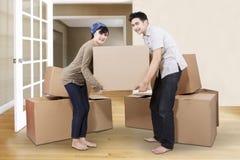 打开纸板的夫妇在新的家 库存照片