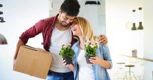 打开纸板箱的年轻夫妇在移动概念的新的家 图库摄影