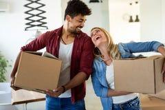 打开纸板箱的年轻夫妇在移动概念的新的家 库存照片