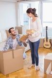 打开纸板箱的逗人喜爱的夫妇 免版税库存照片