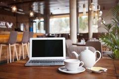 打开网书和茶用在桌上的柠檬在moder咖啡馆/餐馆/酒吧内部 免版税库存图片